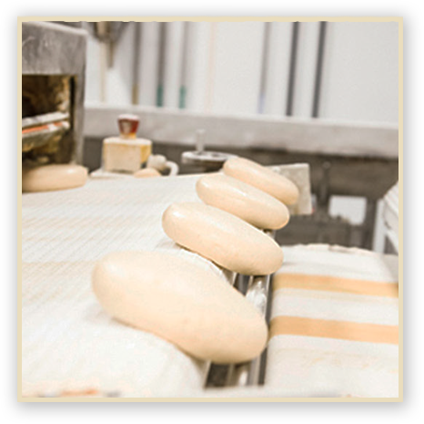 Pizza dough being moved on a conveyor belt